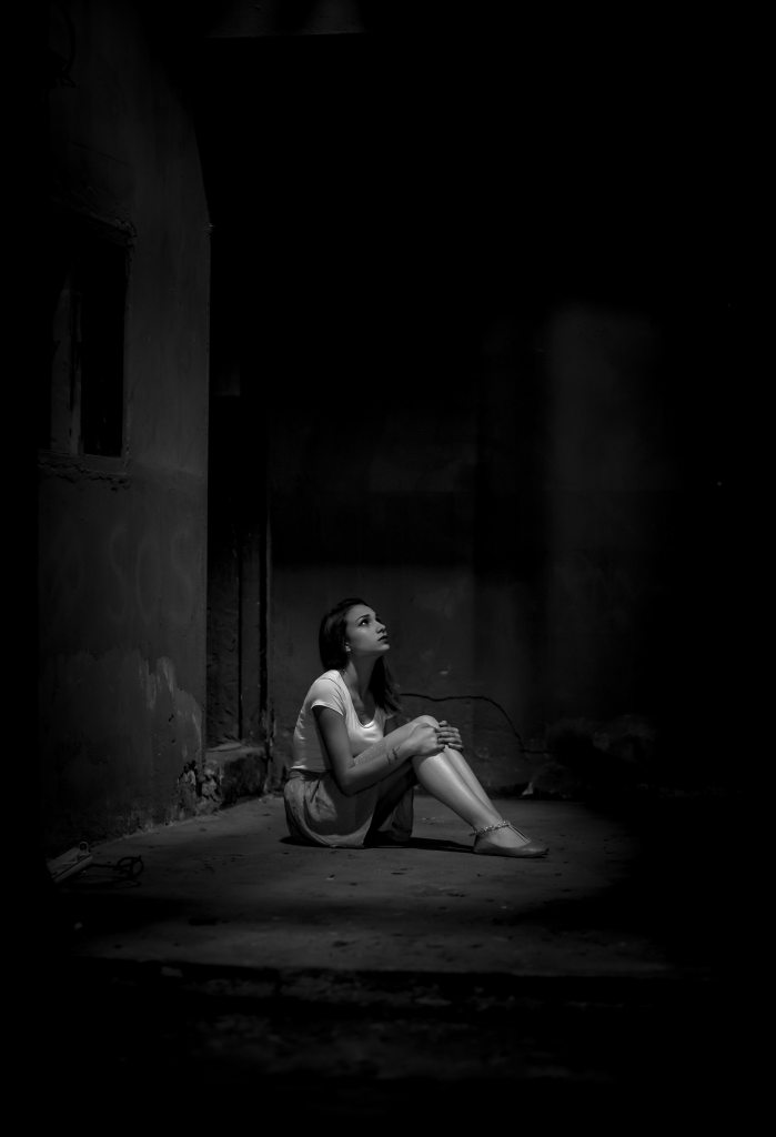 Black and White Photo of Woman Sitting Alone